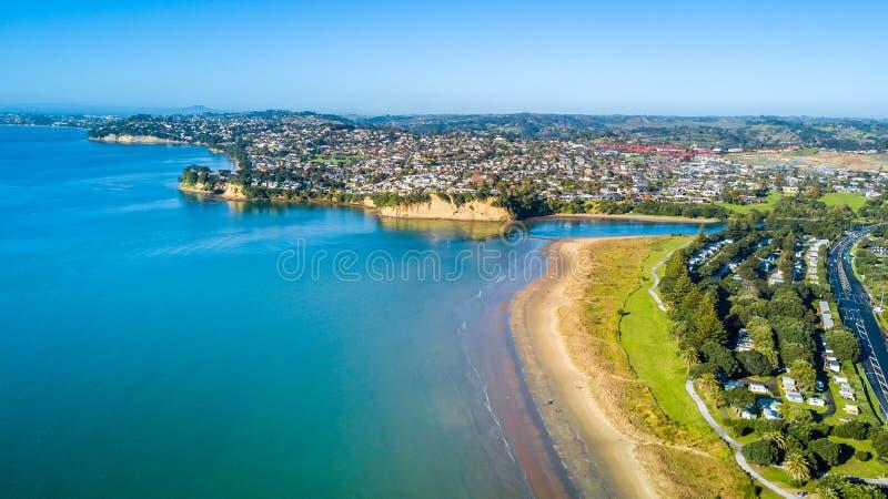 Vista aérea na praia ensolarada com subúrbio residencial no fundo Auckland, Nova Zelândia fotos de stock royalty free