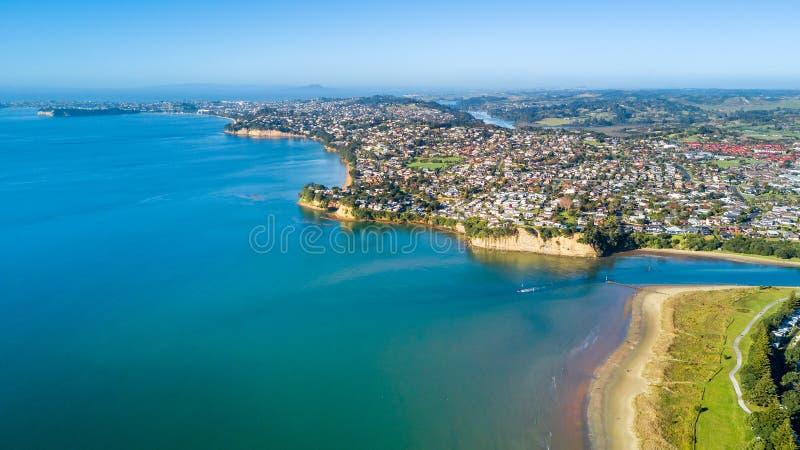 Vista aérea na praia ensolarada com subúrbio residencial no fundo Auckland, Nova Zelândia imagens de stock royalty free