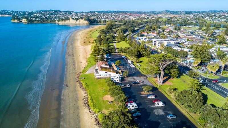 Vista aérea na praia ensolarada com subúrbio residencial no fundo Auckland, Nova Zelândia imagem de stock