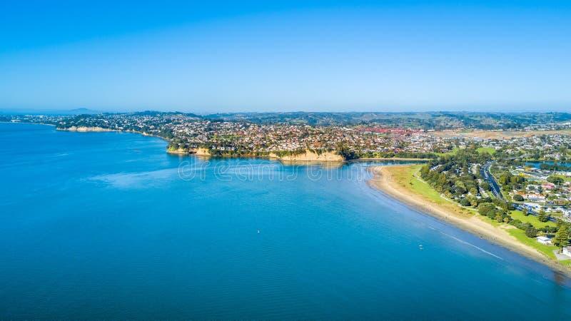 Vista aérea na praia ensolarada com subúrbio residencial no fundo Auckland, Nova Zelândia imagens de stock