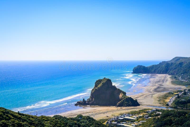 Vista aérea sobre a praia de Piha, Lion Rock poderoso no centro, na costa oeste de Auckland, Nova Zelândia fotografia de stock royalty free