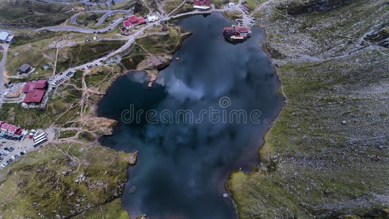 Vista aérea sobre um lago pequeno em um dia tormentoso, na parte superior de montanhas de Fogaras, Trasnsylvania, Romênia imagem de stock