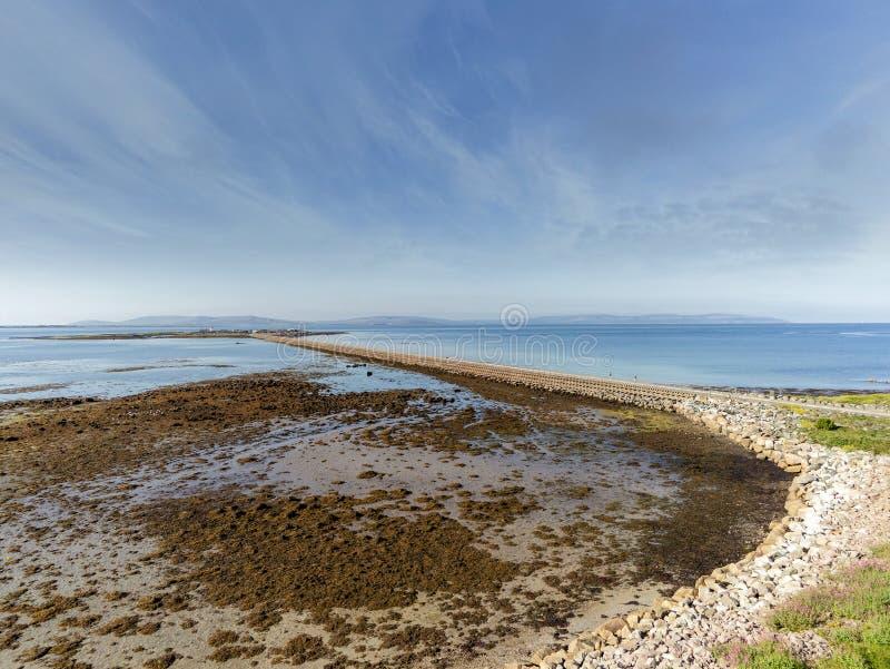 Vista aérea. Via de comunicação conectando a ilha de Mutton com a cidade de Galway. Dia ensolarado quente, céu azul e água do fotos de stock royalty free
