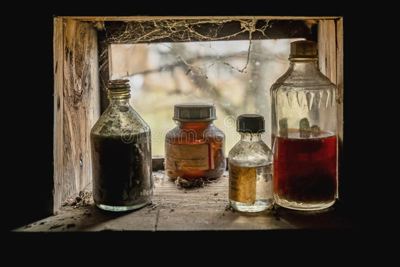 vista abbandonata della finestra con le droghe in contenitori di vetro fotografia stock