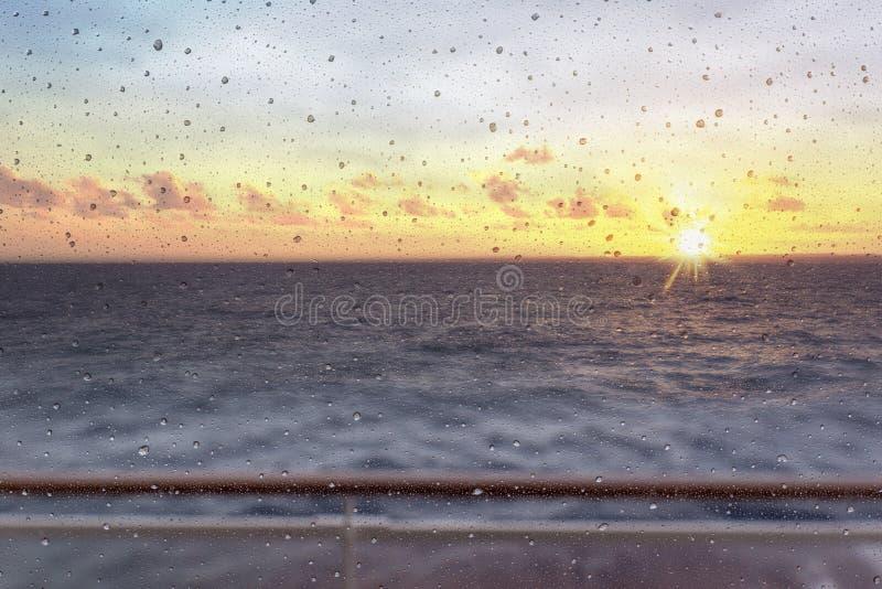 Vista abstracta de las gotitas de la ventana contra el sol poniente y el océano foto de archivo