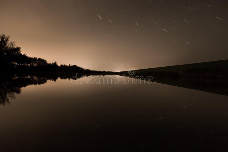 Vista abstracta de un pequeño lago con la reflexión del rastro de la estrella fotografía de archivo libre de regalías