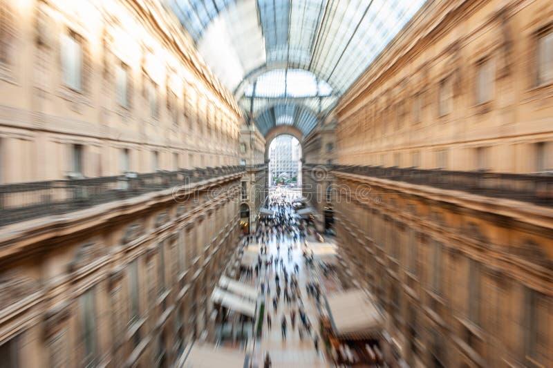 Vista abstracta intencionalmente borrosa del Galleria Vittorio Emanuele II con la gente que hace compras en Milán, Italia imagen de archivo