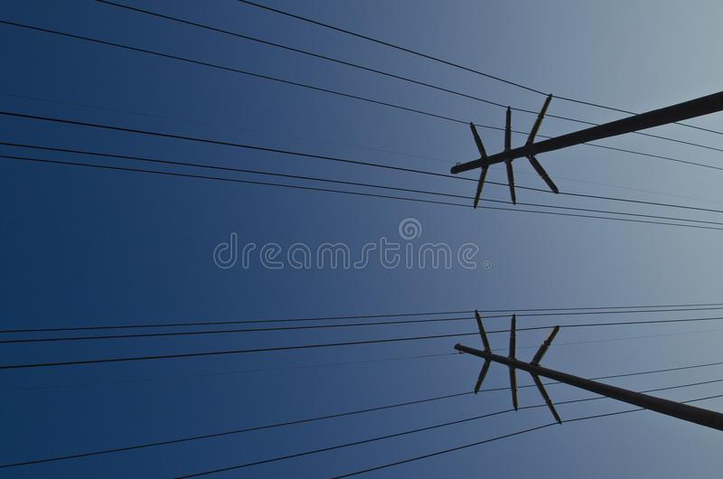 Vista abstracta lateral torcida de las líneas eléctricas en el cielo fotos de archivo