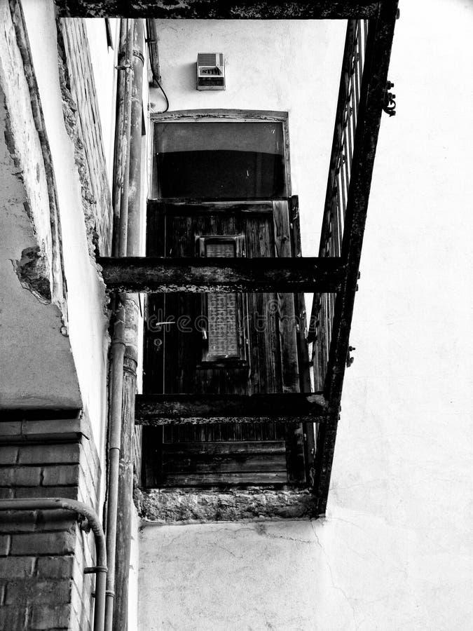 Vista abstrata da laje de cimento demulida e da porta de entrada de madeira fotografia de stock