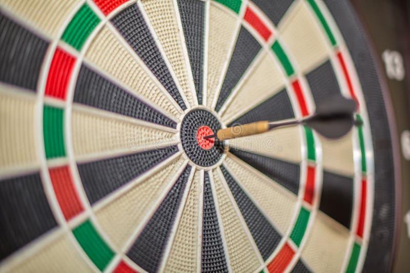 Vista accurata del dardo che colpisce centro dell'obiettivo, del bersaglio e del dardo, fondo vago immagine stock