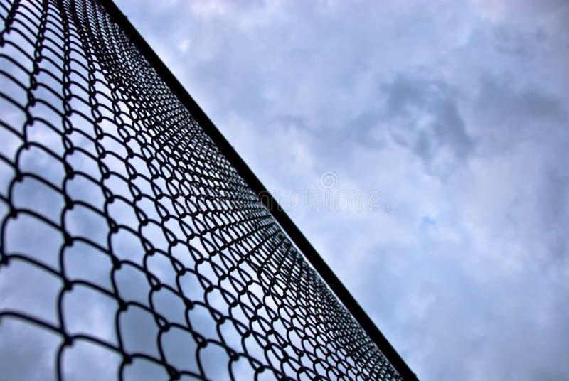Vista acima em um céu sinistro atrás de uma cerca alta imagem de stock
