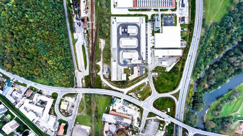 Vista aerea dei fabbricati industriali, della strada principale e di poca città fotografia stock