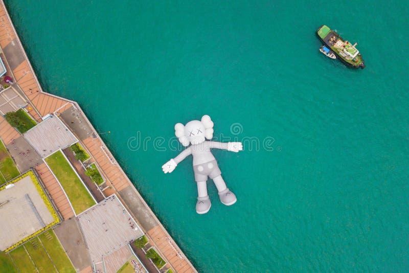 Vista aerea del compagno di KAWS, scultura gigante che galleggia sull'acqua Figura in Victoria Harbour, Hong Kong La Repubblica C immagine stock