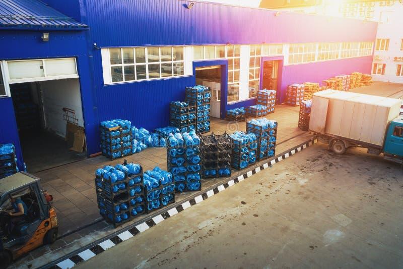 Vista aerea del deposito merci di un impianto o di una fabbrica di acqua potabile alla luce del sole, di rack con bottiglie o gal immagine stock
