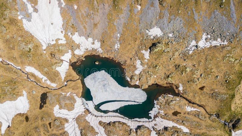 Vista aerea del fuco giù e superiore di un lago naturale alpino durante la stagione primaverile Fusione della neve Alpi italiane  immagine stock libera da diritti