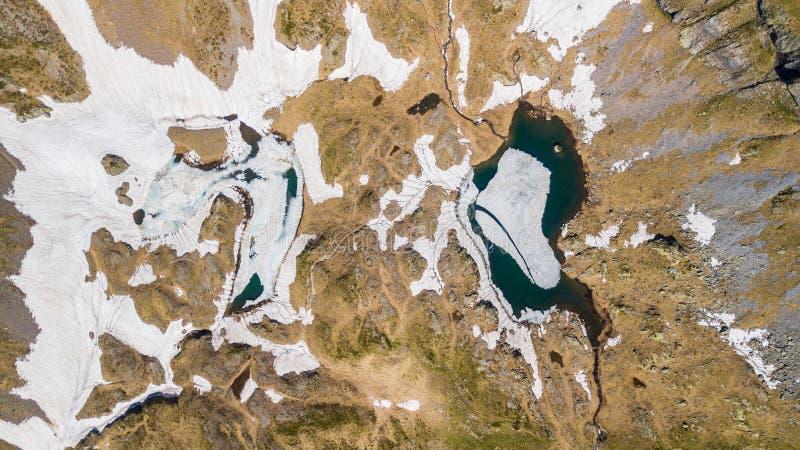 Vista aerea del fuco giù e superiore di un lago naturale alpino durante la stagione primaverile Fusione della neve Alpi italiane  fotografia stock libera da diritti