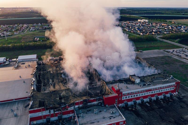 Vista aerea del magazzino industriale bruciato o della costruzione concentrare di logistica dopo il grande fuoco con fumo enorme  fotografia stock libera da diritti