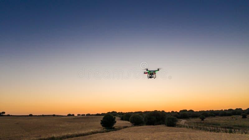Vista aerea del volo del fuco con la macchina fotografica digitale sopra un campo con il tramonto immagini stock