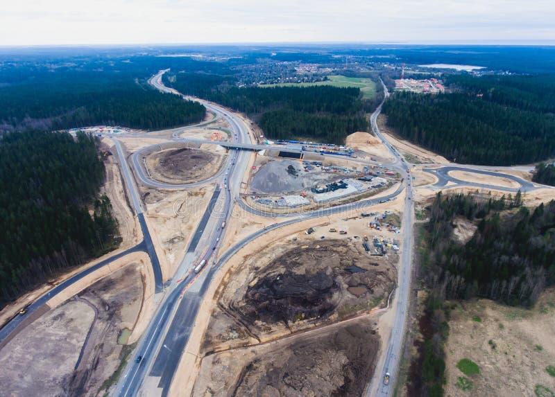 Vista aerea dell'aria di un cantiere massiccio con un veicolo pesante, un bulldozer e un escavatore, sviluppanti una nuovi strada immagine stock libera da diritti