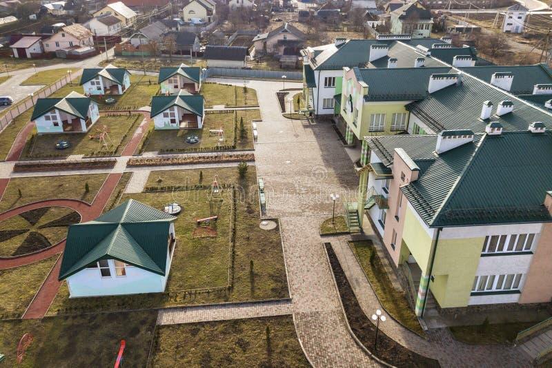 Vista aerea dell'asilo o complesso moderno della scuola, tetti di costruzione decorati e campo da giuoco variopinto sull'iarda so fotografia stock