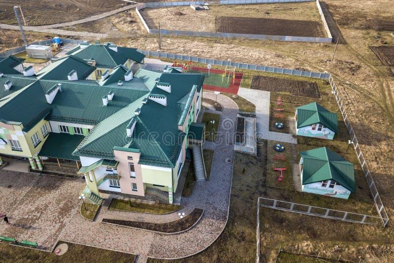 Vista aerea dell'asilo o complesso moderno della scuola, tetti di costruzione decorati e campo da giuoco variopinto sull'iarda so fotografie stock