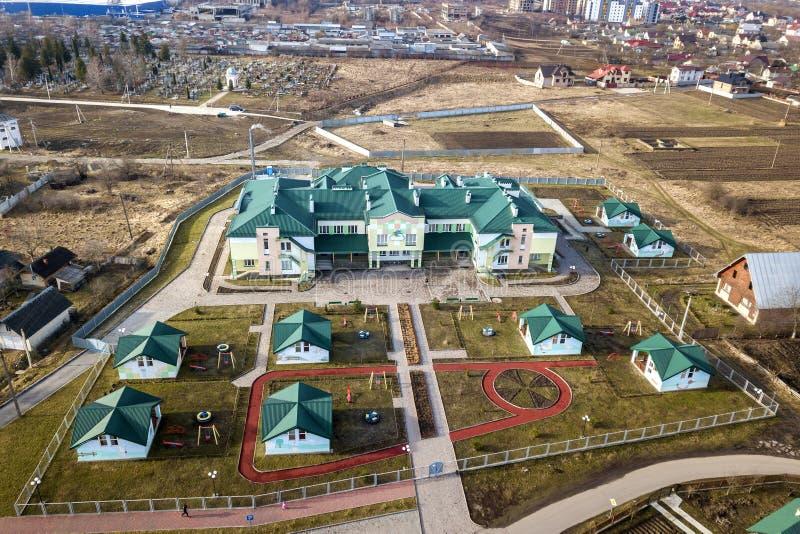 Vista aerea dell'asilo o complesso moderno della scuola, tetti di costruzione decorati e campo da giuoco variopinto sull'iarda so fotografie stock libere da diritti