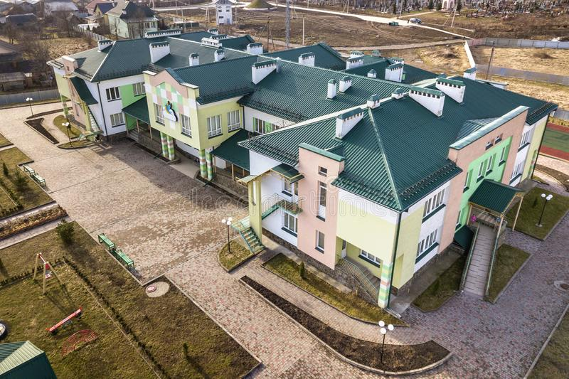 Vista aerea dell'asilo o complesso moderno della scuola, tetti di costruzione decorati e campo da giuoco variopinto sull'iarda so immagine stock libera da diritti