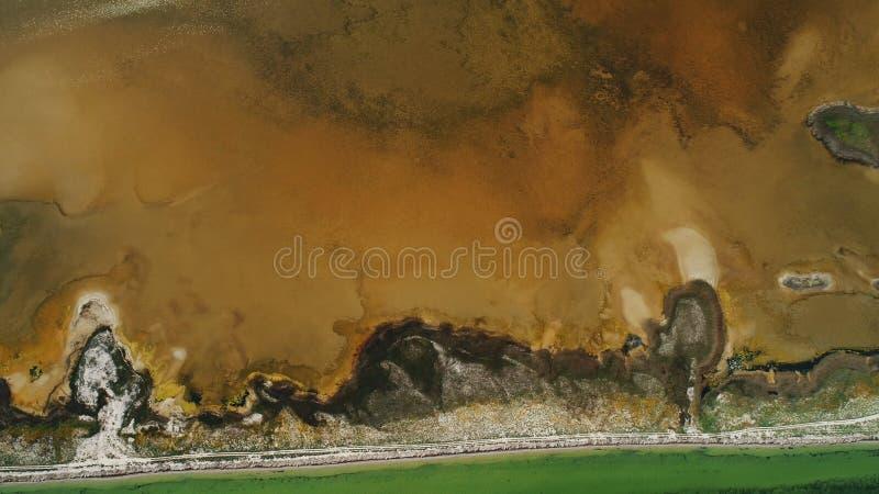 Vista aerea dell'isola scura insolita con terra marrone, le paludi della mangrovia ed i bacini idrici gialli con acqua sporca, co immagini stock libere da diritti