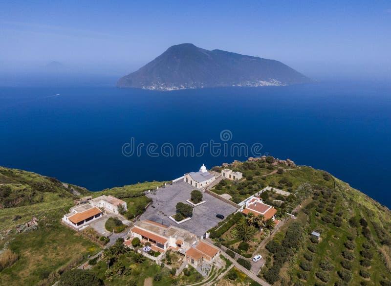 Vista aerea della chiesa nel villaggio di Quattropani sull'isola di Lipari con un'isola della salina nei precedenti fotografia stock