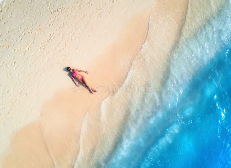 Vista aerea della donna sulla spiaggia sabbiosa al tramonto fotografia stock