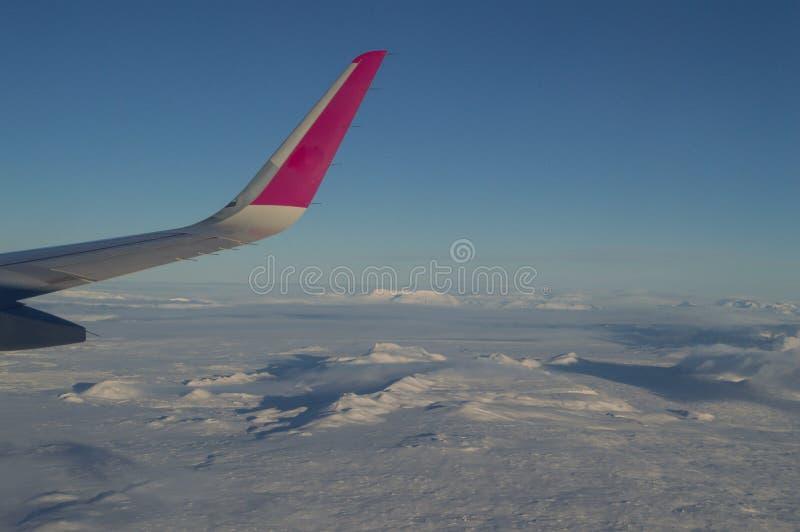 Vista aerea della linea costiera dell'Islanda con l'ala dell'aereo in volo immagine stock