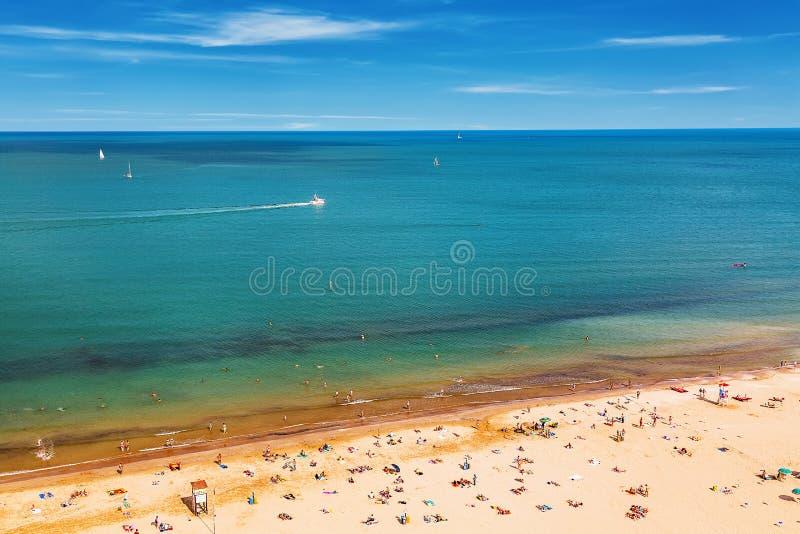 Vista aerea della spiaggia di Rimini con la gente, le navi ed il cielo blu Concetto di vacanze estive immagine stock libera da diritti