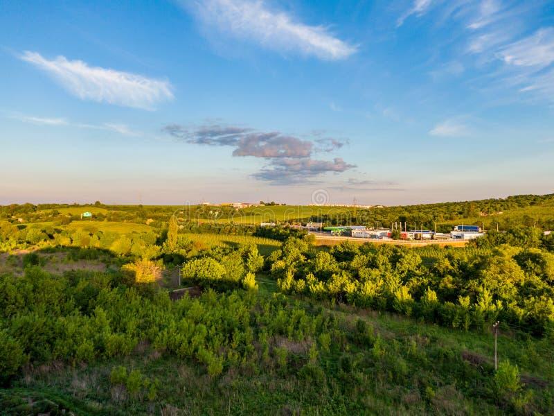 Vista aerea della stazione del combustibile gassoso vicino alla strada Alberi e cespugli verdi in priorit? alta durante il tramon fotografie stock