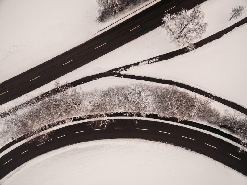 vista aerea della strada asfaltata vuota e delle piante innevate fotografia stock