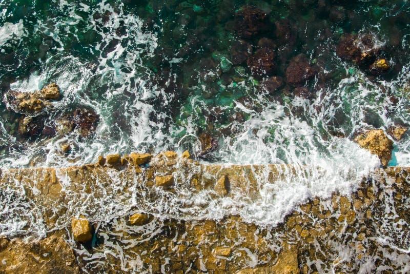 Vista aerea delle onde del mare che lavano sulla costa rocciosa del mare adriatico immagine stock