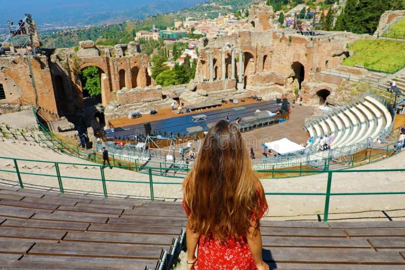 Vista aerea di bella giovane donna che guarda le rovine del teatro del greco antico in Taormina, Sicilia Italia fotografia stock libera da diritti