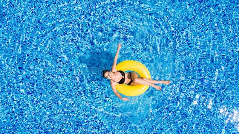 Vista aerea di giovane nuoto castana della donna sul giallo grande gonfiabile nello stagno Punto di vista superiore di signora es fotografie stock libere da diritti