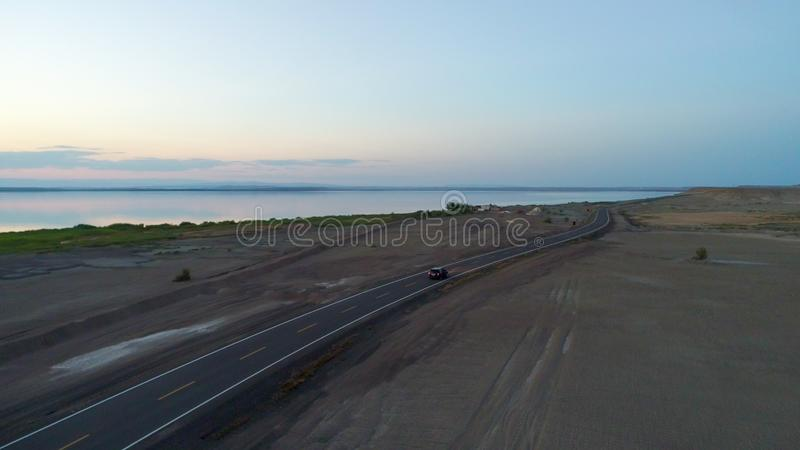 Vista aerea di guida di veicoli durante il tramonto su una strada vuota in mezzo al deserto fotografia stock