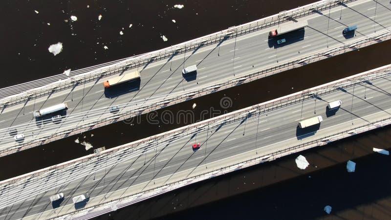 Vista aerea di guida di veicoli e dei camion su un ponte strallato sopra il fiume immagine stock