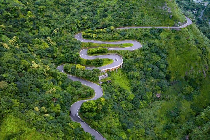 Vista aerea di guida di veicoli sulla strada di zigzag e curva o sulla via sulla collina della montagna con gli alberi forestali  immagini stock