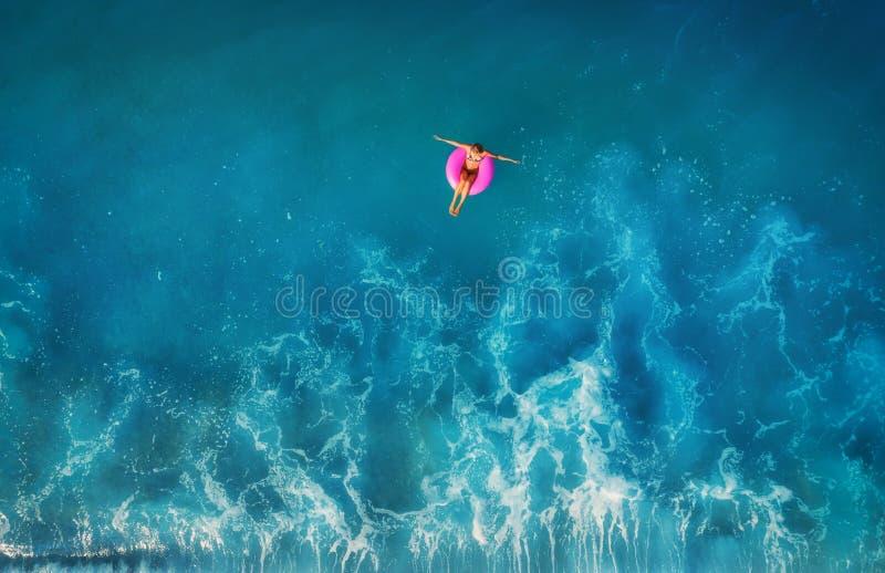 Vista aerea di nuoto della giovane donna sull'anello rosa di nuotata immagine stock
