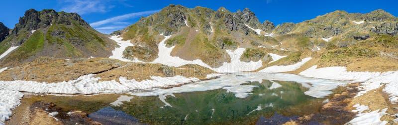Vista aerea di un lago naturale alpino durante la stagione primaverile Fusione della neve Alpi italiane L'Italia fotografie stock