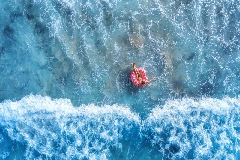 Vista aerea di un nuoto della giovane donna con l'anello di nuotata della ciambella immagine stock