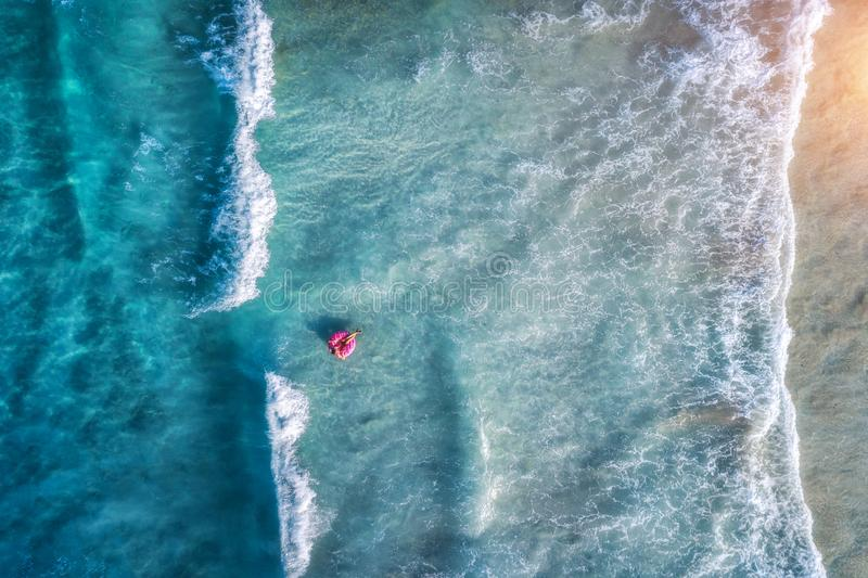 Vista aerea di una donna di nuoto in mare blu con le onde fotografie stock