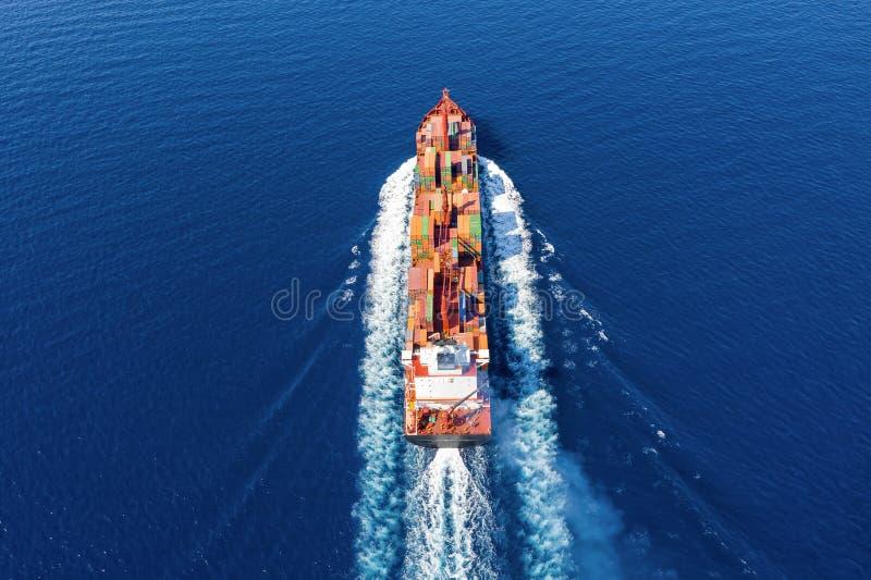Vista aerea di una nave porta-container nel moto sopra l'oceano aperto fotografia stock libera da diritti