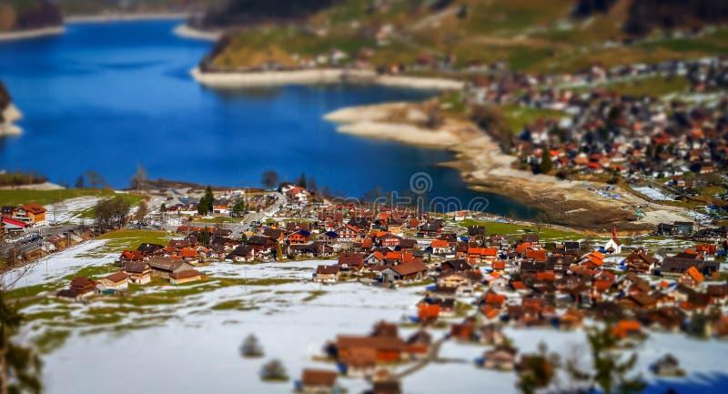 Vista aerea miniatura dello inclinazione-spostamento del villaggio in alpi immagini stock