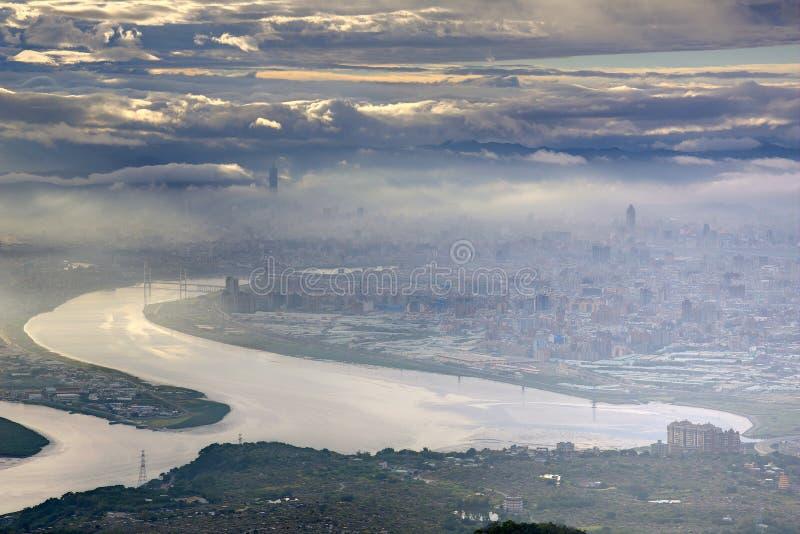 Vista aerea panoramica della città nebbiosa di Taipei dalla riva del fiume fotografie stock