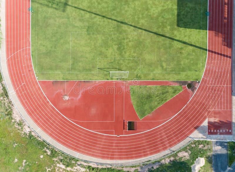Vista aerea sulla metà del campo di calcio, campo di football americano con i numeri sulla pista corrente rossa immagine stock