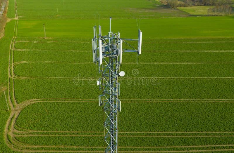 Vista aerea sulla torre d'acciaio di telecomunicazione in mezzo alla radio del campo verde, al telefono ed al segnale di trasmiss immagini stock