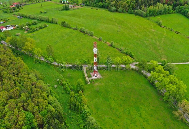 Vista aerea sulla torre d'acciaio di telecomunicazione in terra verde con il prato, la foresta ed il villaggio fotografie stock libere da diritti